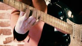 Guitarrista en la etapa que toca los tambores y la guitarra y que canta delante de la cantidad defocused de la pared de ladrillo almacen de video