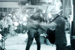 Guitarrista en paseo de la calle en la noche, concepto azul de la falta de definición del tono y de movimiento Fotografía de archivo