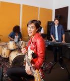 Guitarrista femenino Singing While Performing con la banda imagenes de archivo