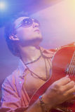 Guitarrista hermoso Playing la guitarra eléctrica Tirado con el estroboscópico Imágenes de archivo libres de regalías
