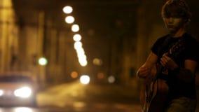 Guitarrista joven del eje de balancín en la calle del tráfico de la noche almacen de metraje de vídeo