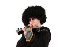 Guitarrista joven que apunta con su guitarra Fotos de archivo