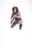 Guitarrista masculino alegre emocionado con la guitarra eléctrica que grita y que salta Imágenes de archivo libres de regalías