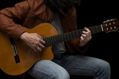 Guitarrista masculino do cabelo longo que joga com a guitarra acústica no couro Fotos de Stock Royalty Free
