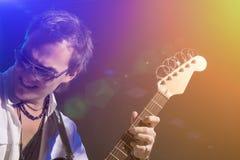 Guitarrista masculino Playing con la expresión Tirado con los estroboscópicos y la ha Imagen de archivo libre de regalías