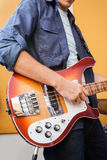 Guitarrista masculino Playing Electric Guitar adentro Imagen de archivo