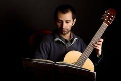 Guitarrista que estudia con el soporte de música imagenes de archivo