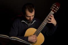 Guitarrista que estudia con la hoja de música Fotos de archivo libres de regalías