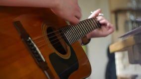 Guitarrista que joga a guitarra acústica - mãos dos guitarristas filme