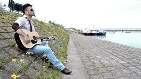 Guitarrista que joga a guitarra perto do rio video estoque