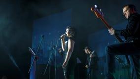 Guitarrista que juega en etapa con la hembra del cantante del piano del grupo almacen de video