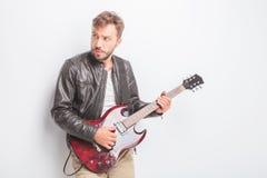Guitarrista que juega una guitarra eléctrica y miradas a su lado Imagen de archivo