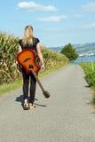 Guitarrista que recorre abajo de la carretera nacional Imagen de archivo libre de regalías