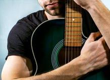 Guitarrista que sostiene una guitarra acústica Foto de archivo