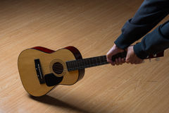 Guitarrista que tenta destruir seu instrumento, sobre o branco imagens de stock