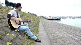 Guitarrista que toca la guitarra cerca del río almacen de metraje de vídeo