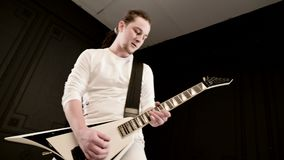 Guitarrista a solas elegante con los dreadlocks en su cabeza y en la ropa blanca en jugar negro del fondo expresivo almacen de metraje de vídeo