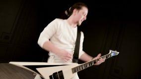Guitarrista a solas elegante con los dreadlocks en su cabeza y en la ropa blanca en jugar negro del fondo expresivo metrajes