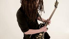 Guitarrista a solas elegante con los dreadlocks en su cabeza y en ropa negra en jugar blanco del fondo expresivo metrajes