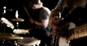 Guitarrista y batería que se realizan junto almacen de video
