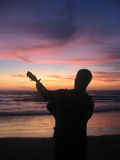 Guitarrista y una puesta del sol Fotografía de archivo