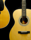 Guitars. Two acoustic guitars with black background forming an S curve royalty free stock photo