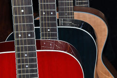 Guitars isolated on black background. Three acoustic six string flat top guitars. Red, black & natural wood colored isolated on a black background. Guitars Royalty Free Stock Images