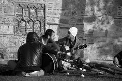 Guitars and music. Men sitting near The White Tower playing music Royalty Free Stock Photos
