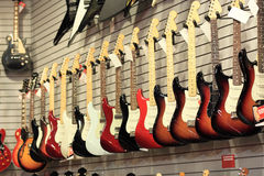 Guitars for Sale on Wall. Row of electric guitars for sale in music shop hanging on wall Royalty Free Stock Image