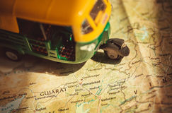 Gujarat on India roads map with driving toy model of auto-rickshaw vehicle.  royalty free stock photography