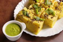 Indian Food - Gujarati Khaman Dhokla. Gujarati Indian Snack, soft and fluffy, Khaman Dhokla with a bowl full of spicy green chutney Royalty Free Stock Photography