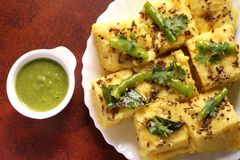 Indian Food - Gujarati Khaman Dhokla. Gujarati Indian Snack, soft and fluffy, Khaman Dhokla with a bowl full of spicy green chutney Royalty Free Stock Photos