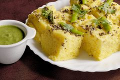Indian Food - Gujarati Khaman Dhokla. Gujarati Indian Snack, soft and fluffy, Khaman Dhokla with a bowl full of spicy green chutney Royalty Free Stock Image