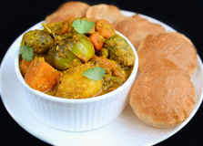 Gujarati main course Indian meal. Gujarati meal in India- Undhiyu and Poori fried flat bread served in main course during Diwali festival and daily routine Royalty Free Stock Photo