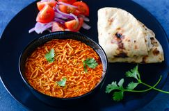 Gujarati meal-Sev tomato nu shak with roti. Gujarati Thali consisting of roti or flatbread and Tomato Sev curry also known as Sev Tamata nu shak and salad stock image