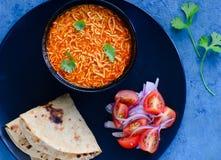 Gujarati cuisine main course-Sev tomato nu shak with roti. Gujarati Thali consisting of roti or flatbread and Tomato Sev curry also known as Sev Tamata nu shak royalty free stock photos