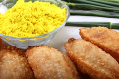Gujia in plate with yellow holi color in bowl Royalty Free Stock Image