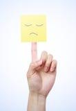 Gul anmärkning med den ledsna framsidan på fingret Arkivfoton