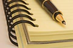 Gul anteckningsbok och penna royaltyfri foto