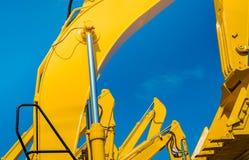 Gul backhoe med den hydrauliska pistongarmen mot klar blå himmel Tung maskin för utgrävning i konstruktionsplats Hydraulisk mach arkivbilder