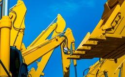 Gul backhoe med den hydrauliska pistongarmen mot klar blå himmel Tung maskin för utgrävning i konstruktionsplats hydrauliskt arkivbild