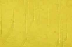 Gul bakgrund för textur för målarfärgdroppandevägg Arkivfoto