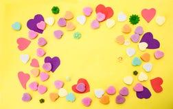 Gul bakgrund med det färgrika snittet ut och godishjärtor i mestadels pinks och purples och några mycket små blommor - hyra rum f royaltyfria bilder