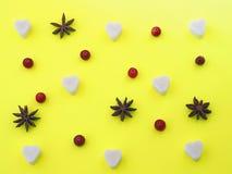Gul bakgrund med sockerhjärta, anisstjärnor och tranbär Arkivbild