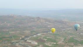 Gul ballong för varm luft som flyger över Cappadocia stock video