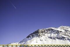 Gul barriär framme av ett snöig berg arkivfoto