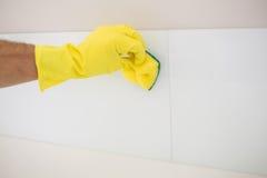 Gul behandskad hand med svampen som gör ren golvet Arkivfoto