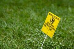 Gul bekämpningsmedelapplikationvarning på grön gräsmatta royaltyfri fotografi