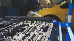 Gul bil för mekanikerreparationer i yrkesmässig automatiskservice som de-fokuseras royaltyfri bild