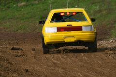 Gul bil på spåret som går snabbt och kastar smuts i luften Arkivbilder